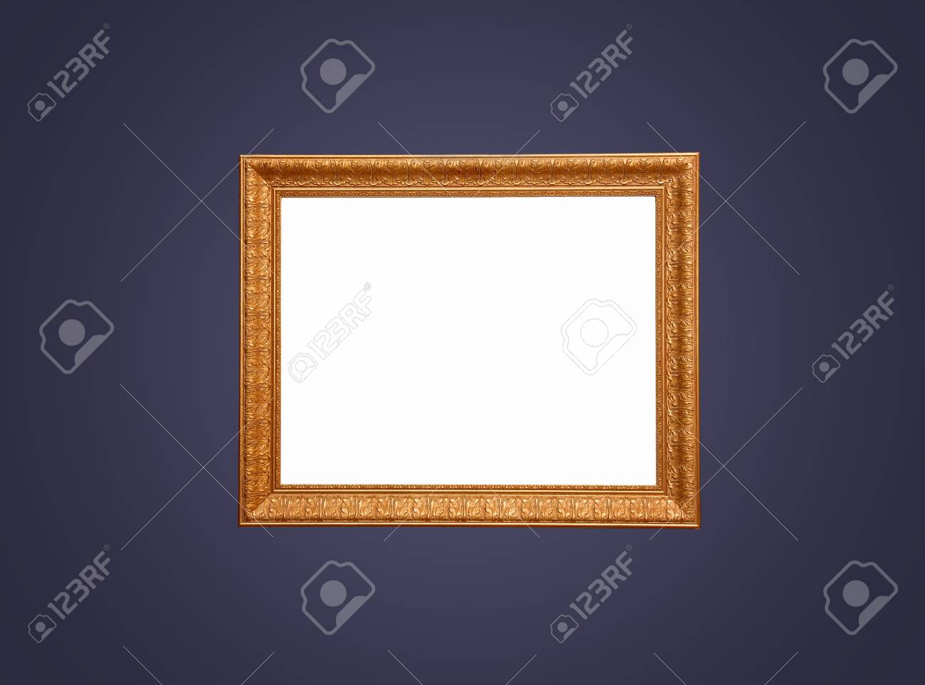 An wood and gold leaf empty frame for painting on a dark blue background. - 43271240
