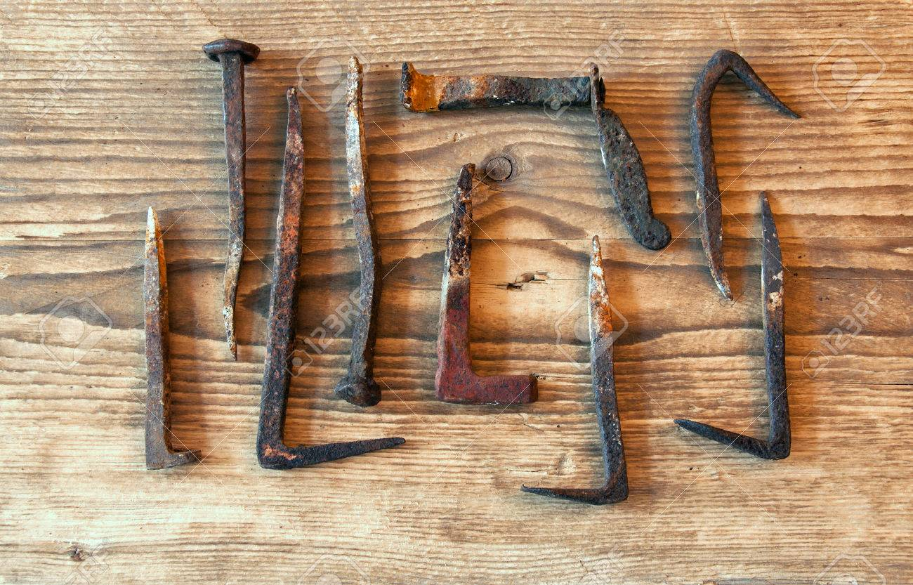 Set of rusty old big nails on a wooden background - 43271250