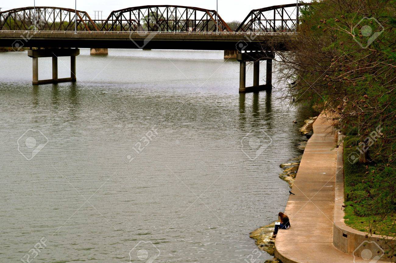 Waco woman reads on bank of river - 16150960