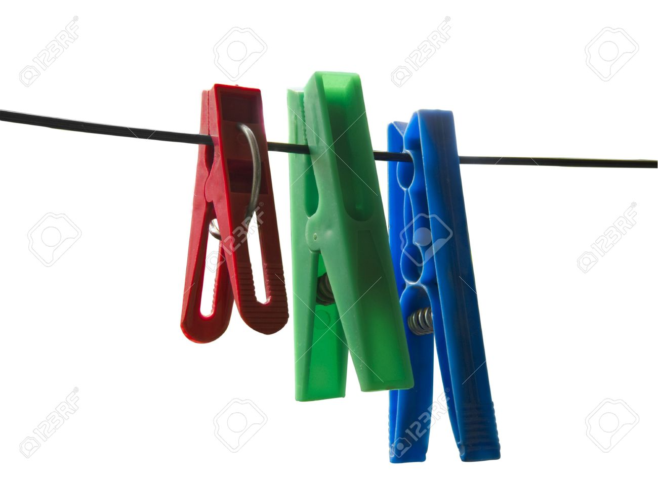 Three Plastic Clips, Red, Green And Blue Hanging On The Clothesline On A  White