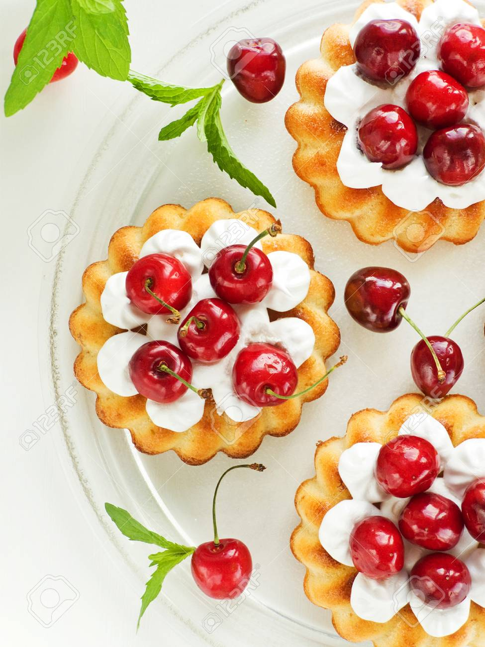 Coconut cakes with whipped cream and sweet cherry. Viewed from above. Stock Photo - 20322093