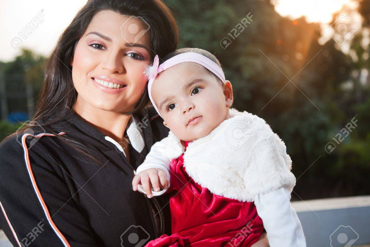 Indian family portrait of indian mother with little baby girl in outdoors stock photo