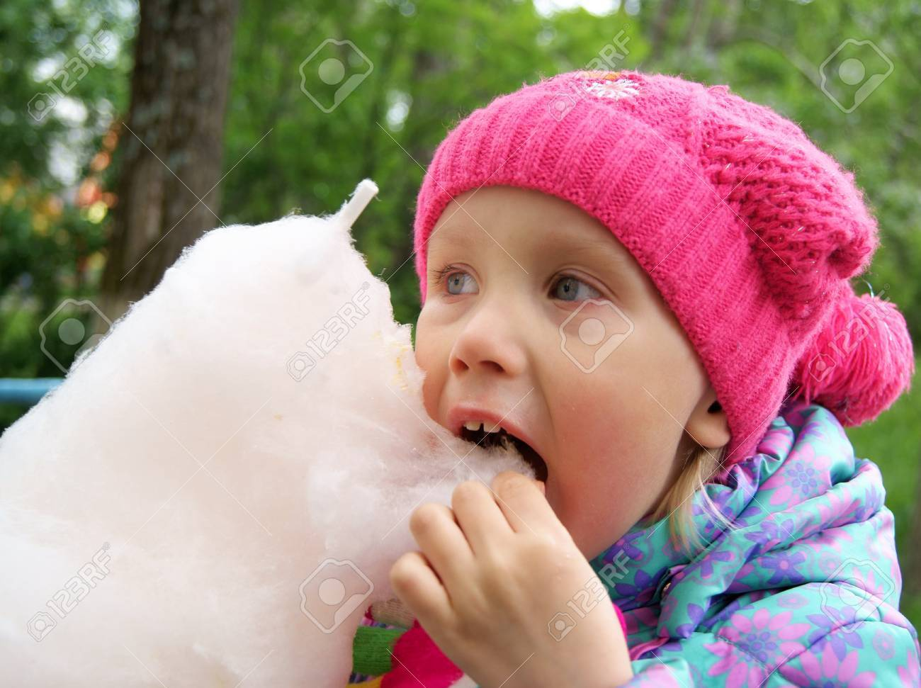 Little girl eats a cotton candy in the park Stock Photo - 10180845