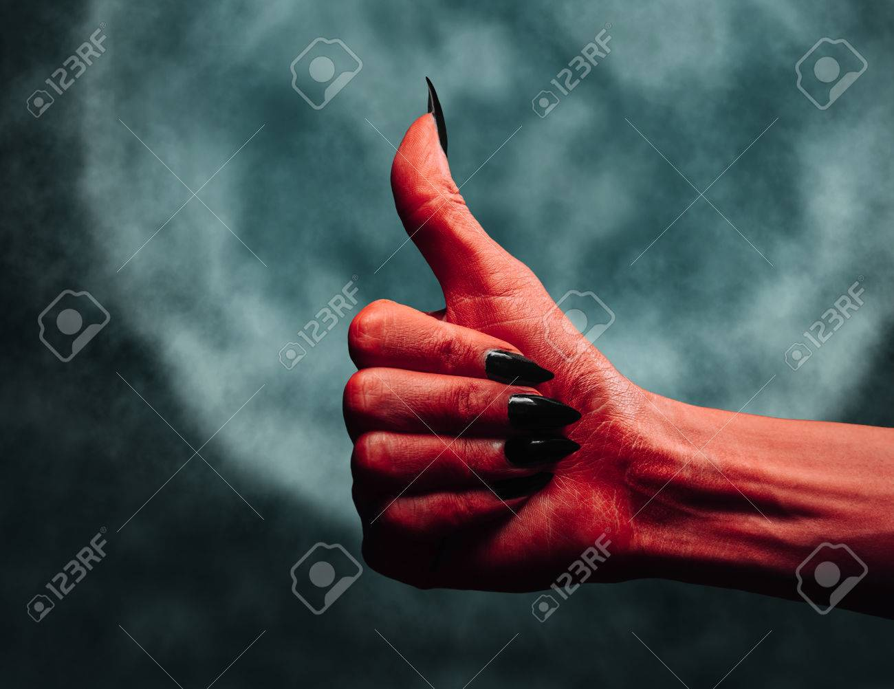red demon or devil hand with thumb up gesture on full moon