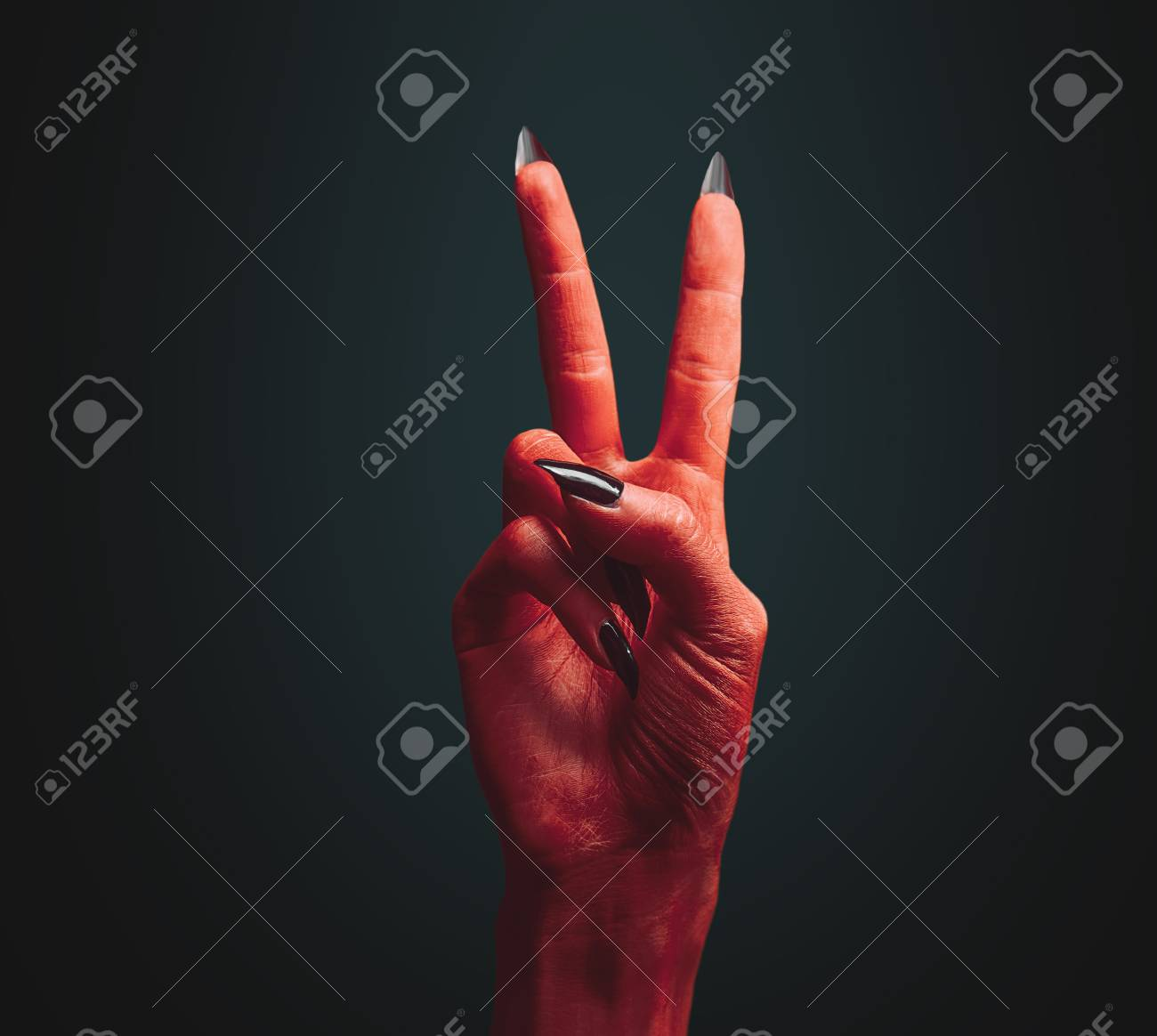 red devil hand on dark peace hand sign halloween or horror