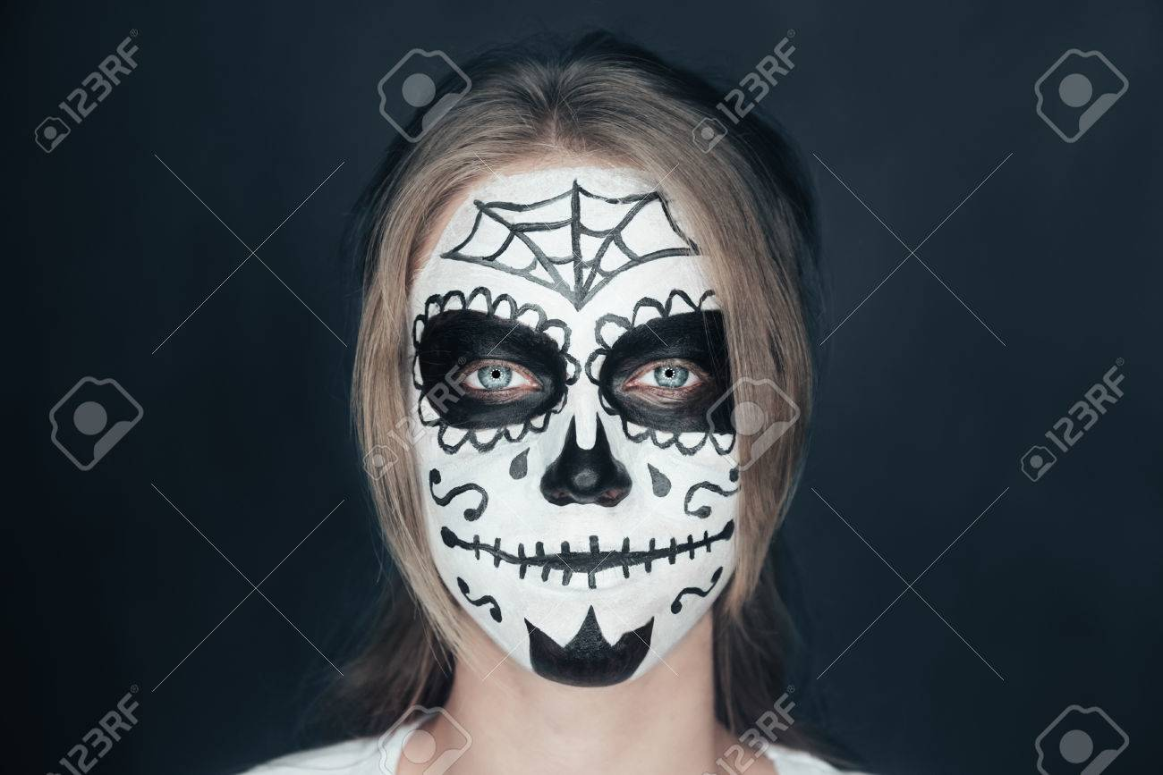 portrait of smiling young woman with sugar skull makeup halloween face art stock photo