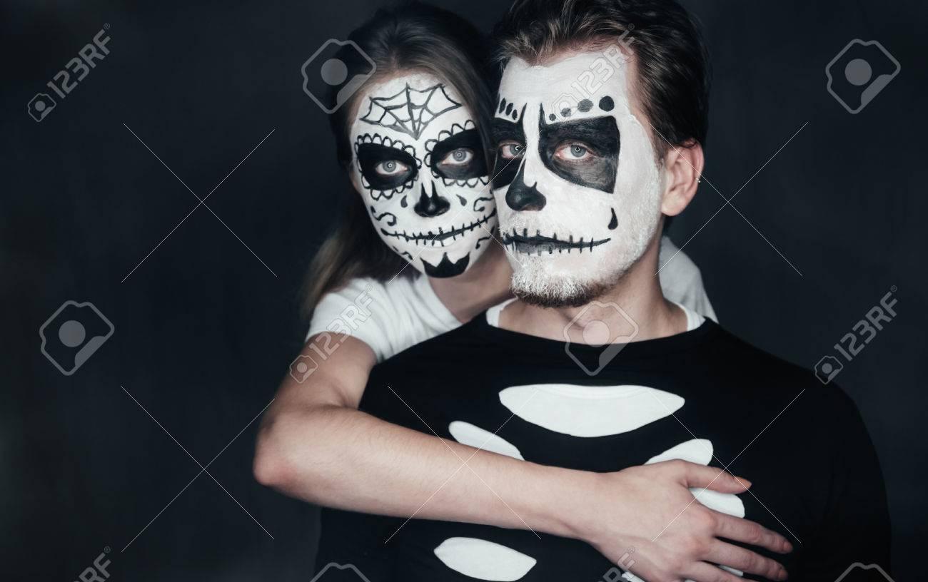 couple in love with dark skull makeup on black halloween face art stock photo