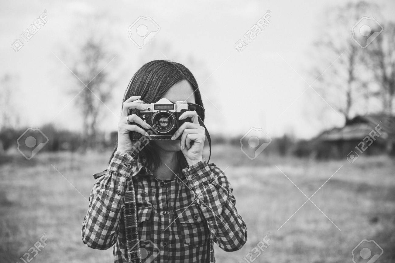 Girl takes photographs with vintage photo camera outdoor with