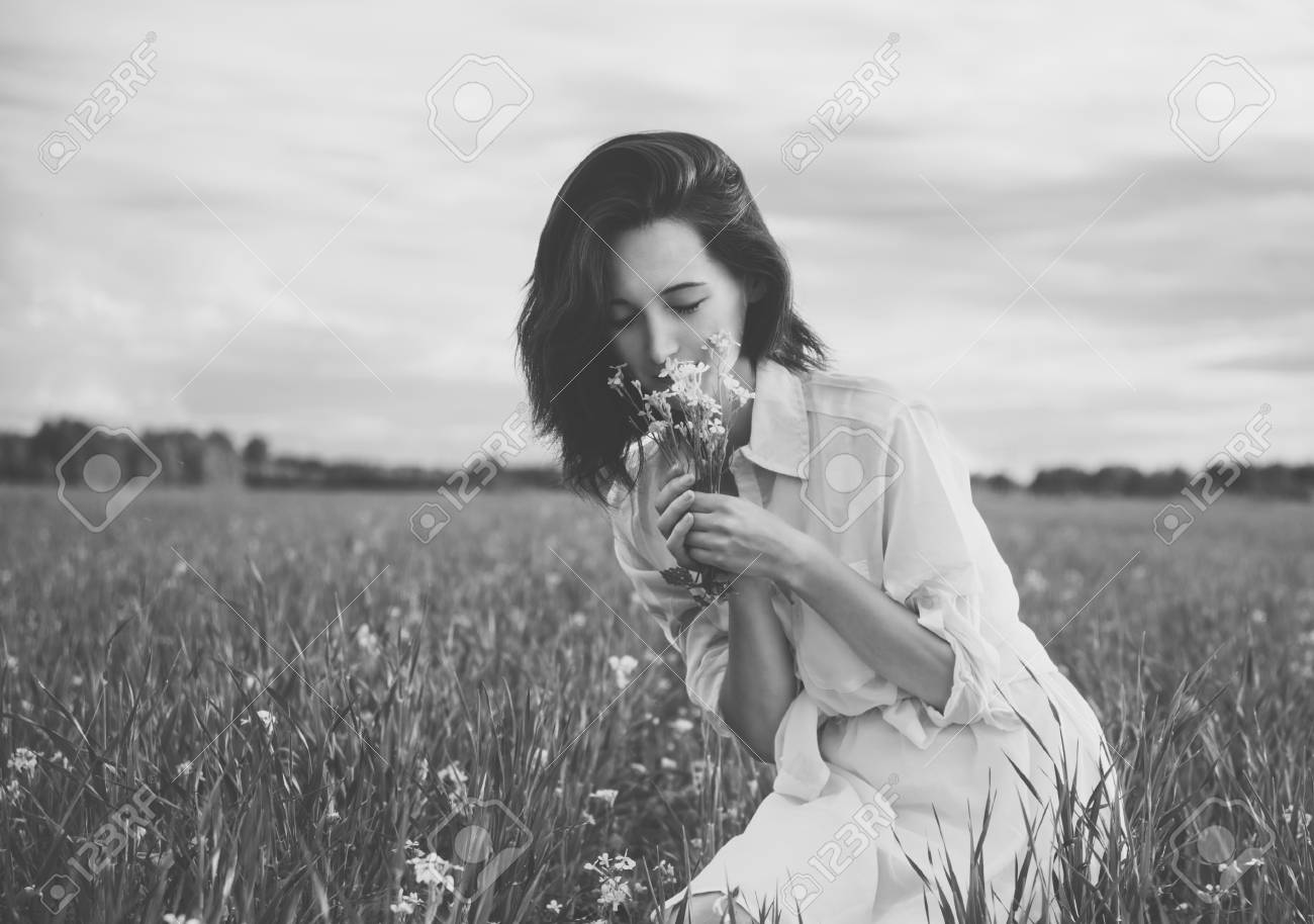Young beautiful woman picking flowers in a summer meadow with