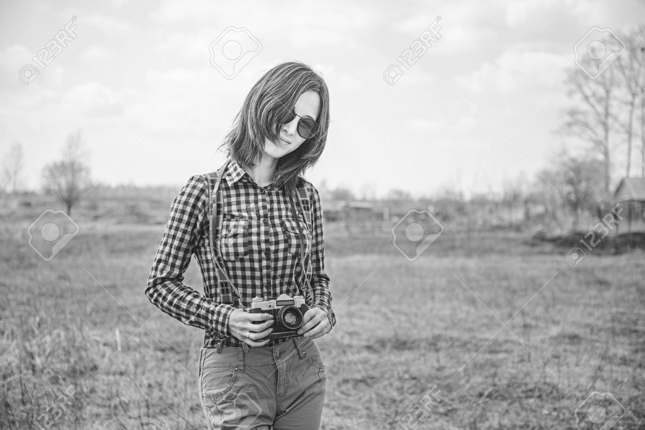 Happy hipster girl with vintage photo camera on nature with film grain and low contrast
