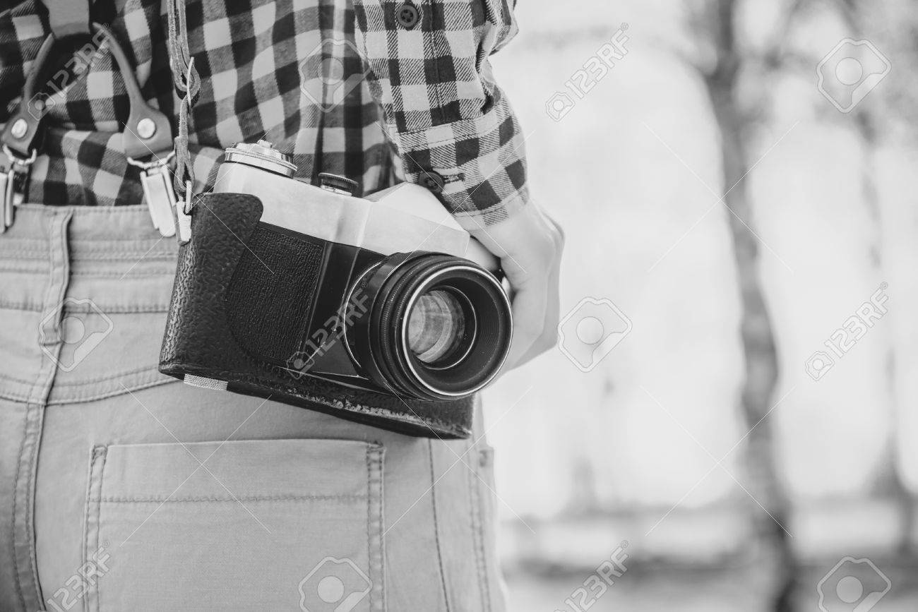 Old photo camera is hanging on female shoulder with film grain and low contrast effect