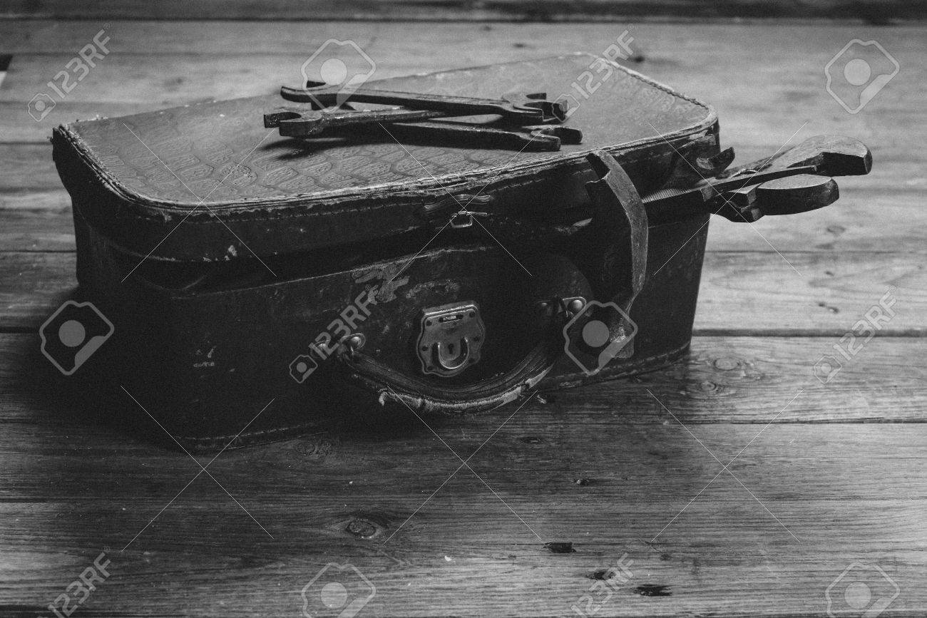 Working tools in vintage case on a wooden table with film grain