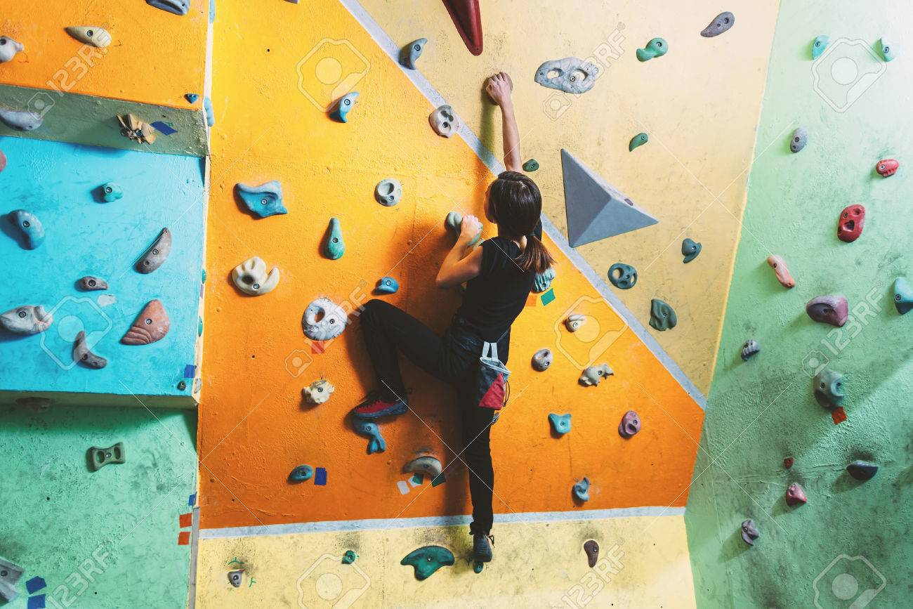 Girl climbing up on practice wall in gym, rear view - 35640653