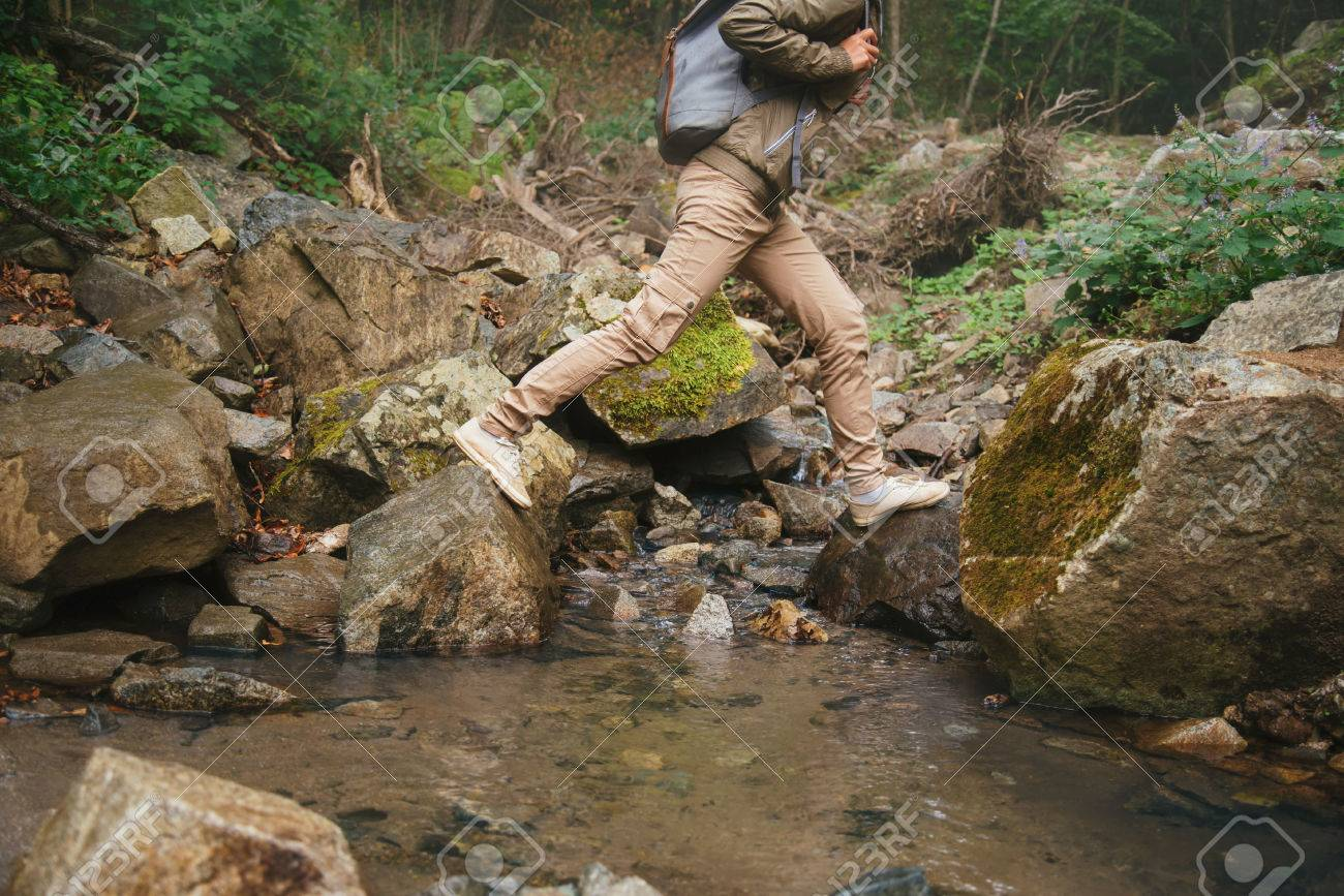 Hiker woman crossing a creek on stones in summer forest, view of legs - 36559660