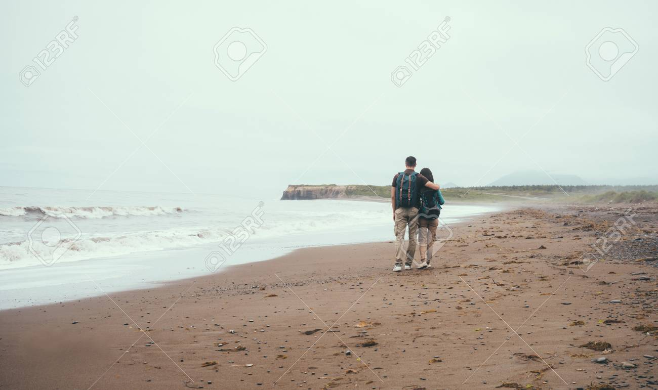 Couple De Dos traveler loving couple with backpacks walking on beach near the