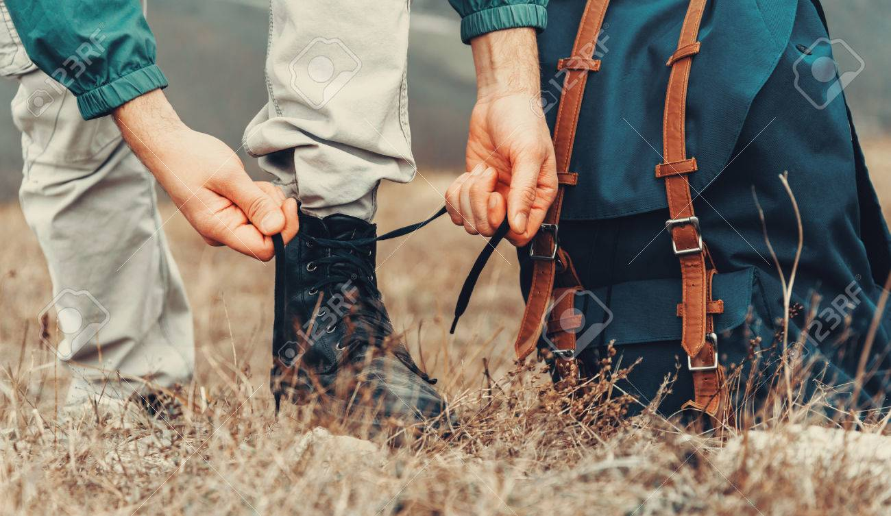 Hiker man tying shoelaces on nature outdoor, near backpack. View of legs. Hiking and leisure theme - 37764036