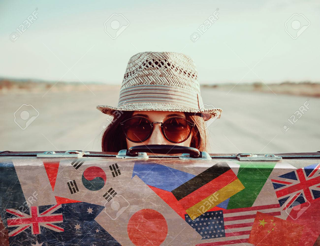 Hipster girl in a hat and sunglasses looks out from vintage suitcase. Suitcase with stamps flags of different country - 38610009
