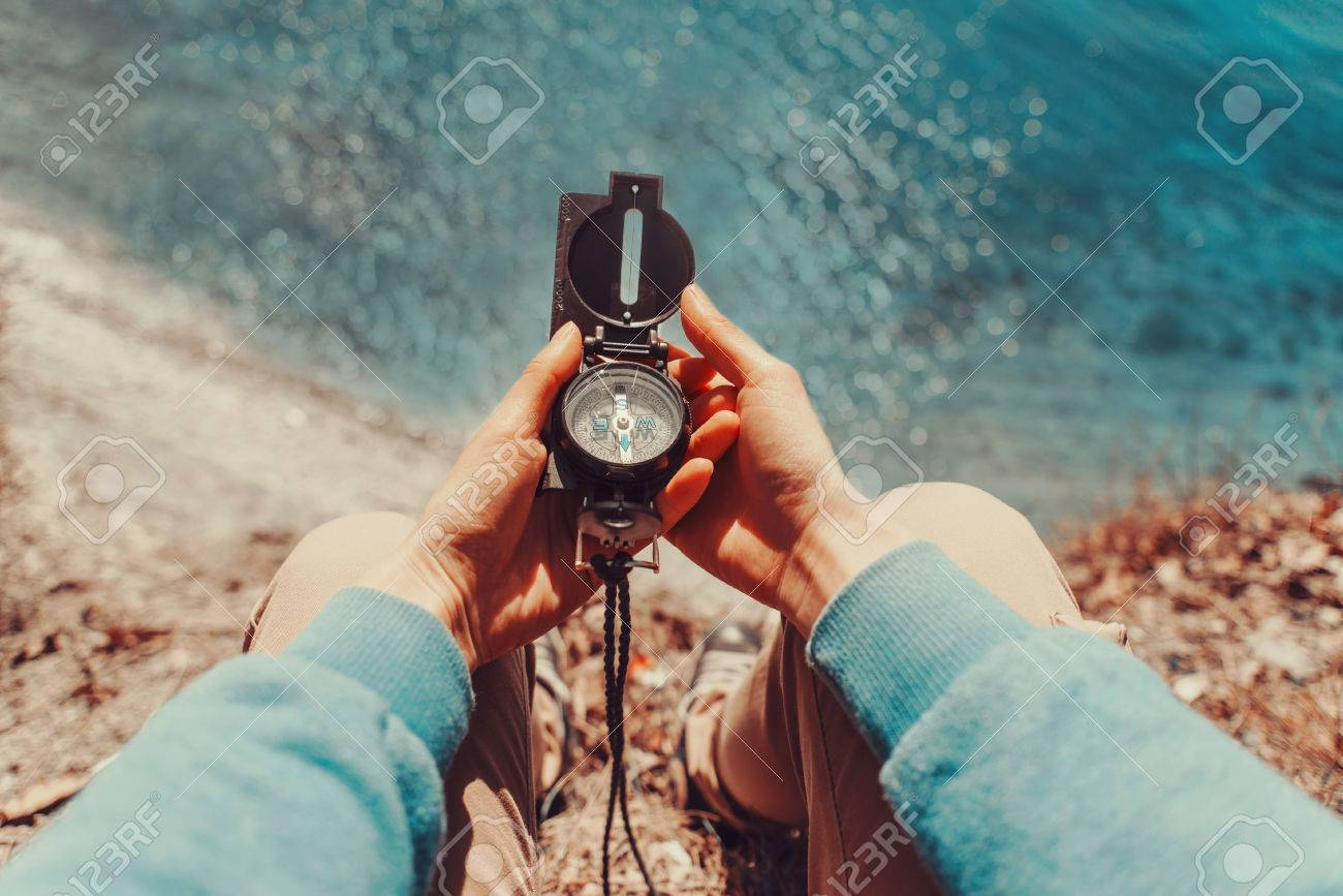 Traveler woman searching direction with a compass on coastline near the sea. Point of view shot - 38610171