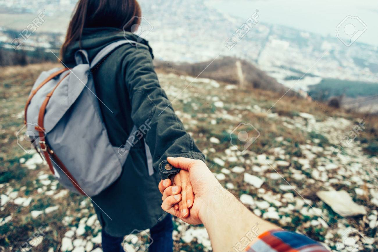 Hiker young woman holding man\'s hand and leading him on nature outdoor. - 38979591