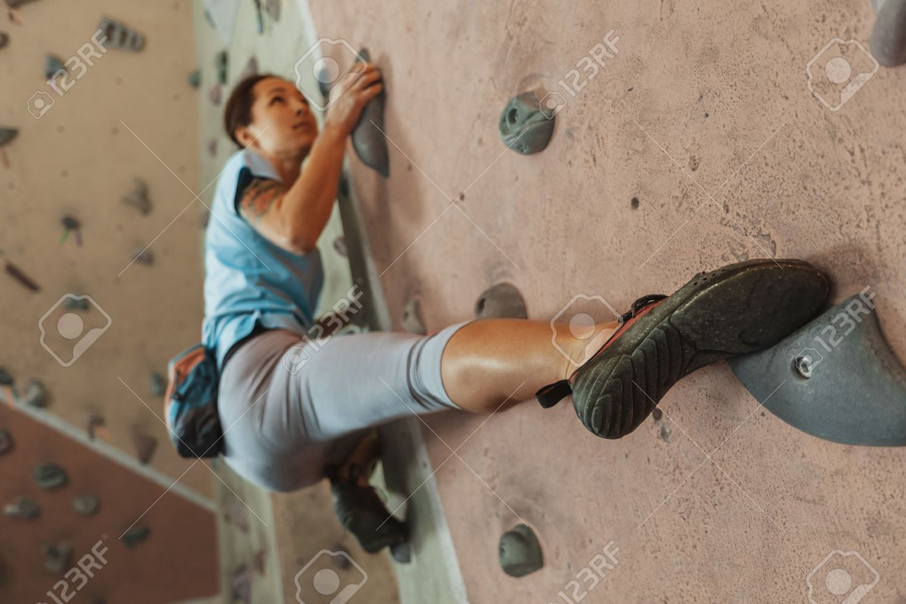 Free climber young woman climbing on practical wall indoor, bouldering - 40869433