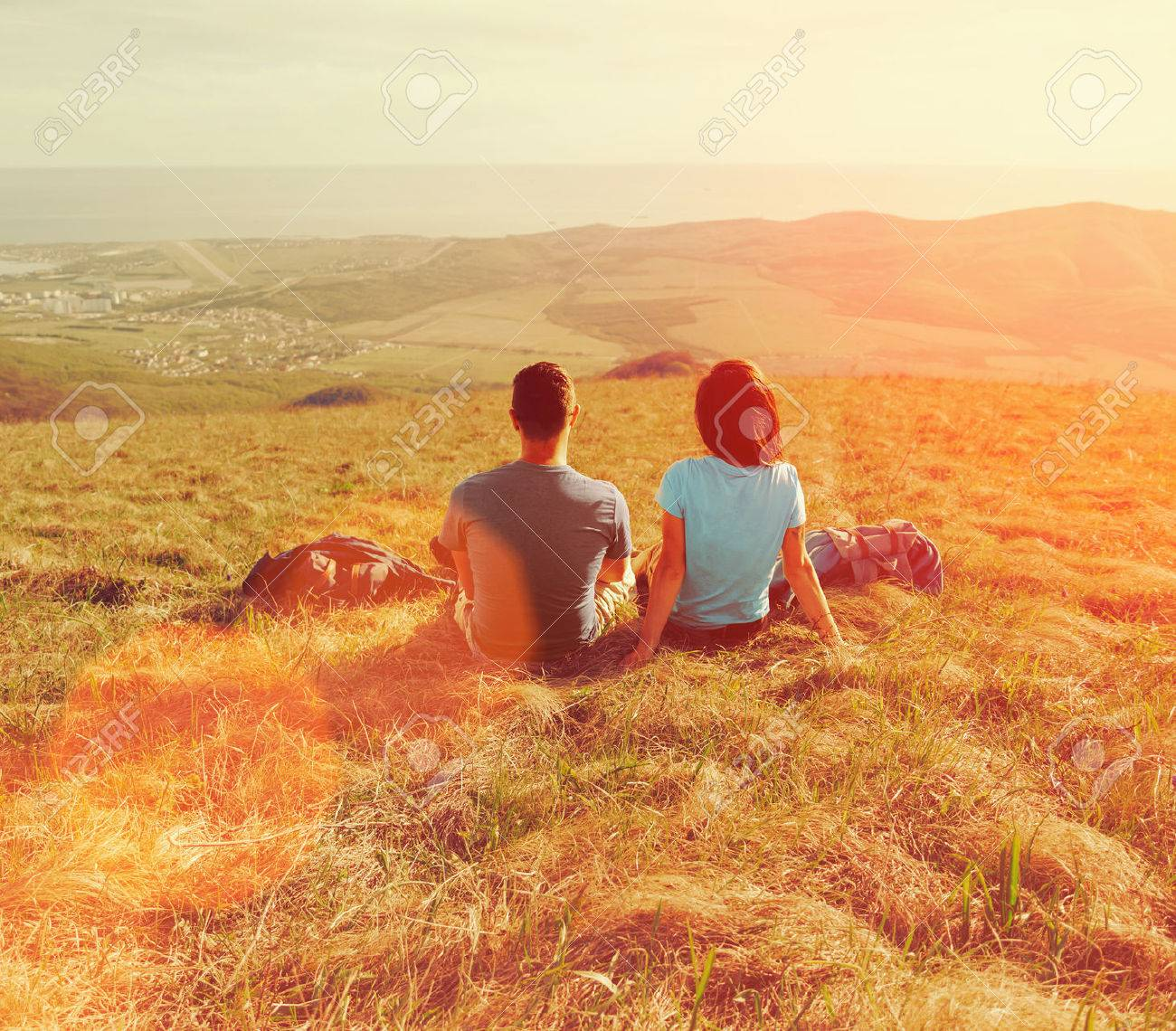 Loving couple sitting on mountain meadow and enjoying view of nature at sunny day in summer Stock Photo - 41121673