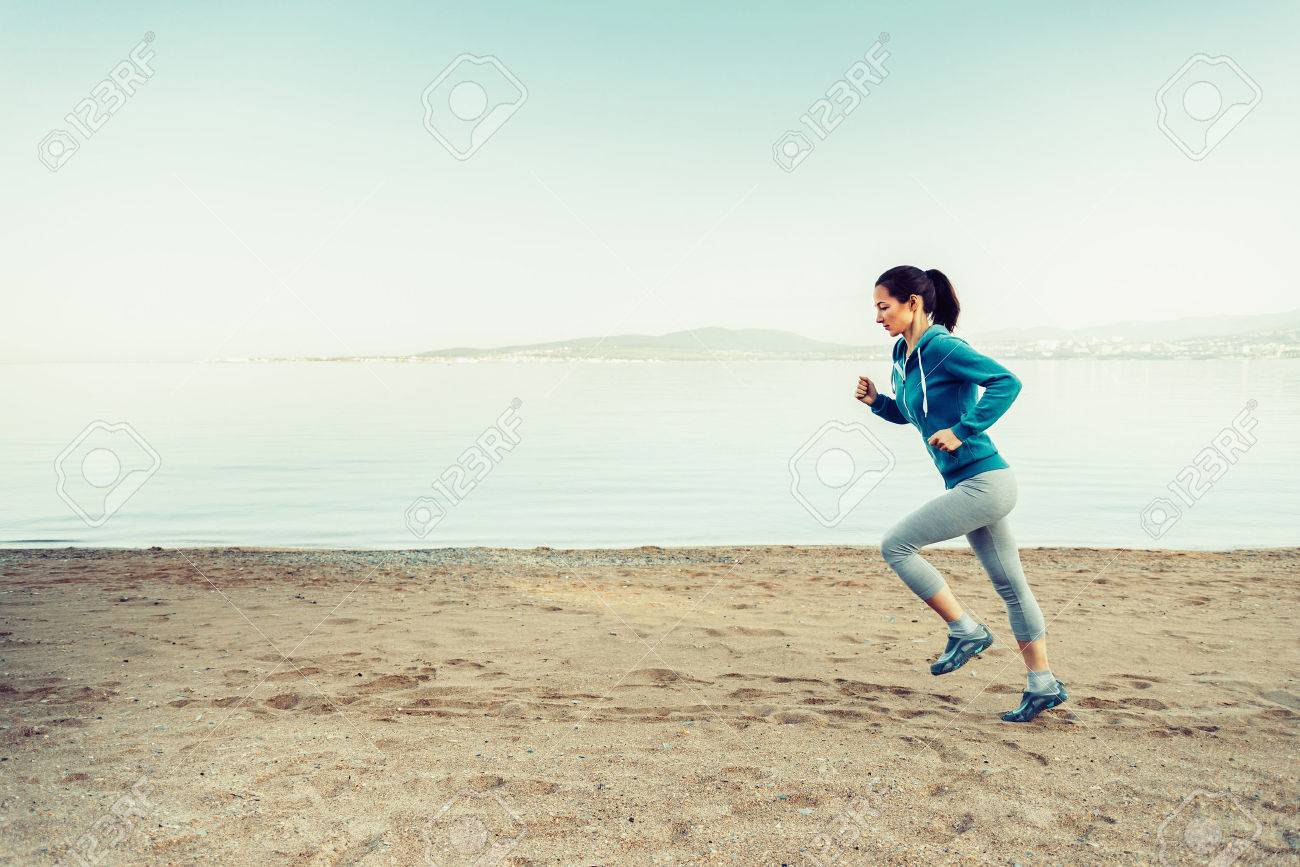 girl running on sand beach near the sea in summer in the morning