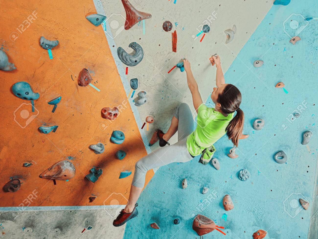 Beautiful sporty young woman climbing on practical wall in gym, bouldering - 41544008
