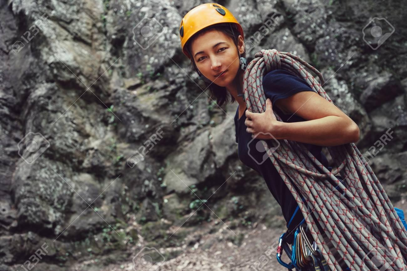 Kletterausrüstung In Der Nähe : Lächelnde junge frau mit kletterausrüstung und seil vor einem