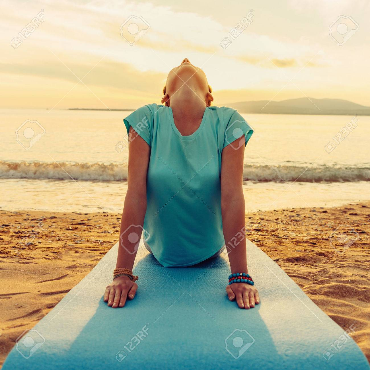 Young woman practicing yoga in upward facing dog pose on beach near the sea on sunset, front view - 49153962