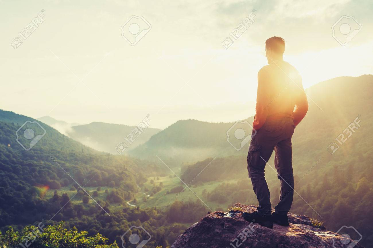Traveler young man standing in the summer mountains at sunset and enjoying view of nature. Image with color - 62427681