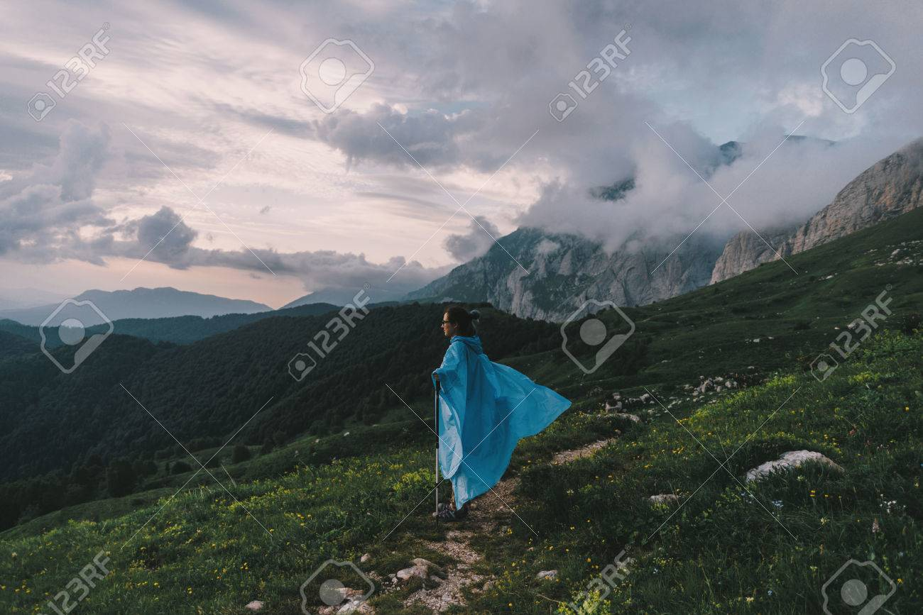 Hiker young woman wearing in raincoat with trekking poles walking in summer mountains at sunset. Stock Photo - 76576644