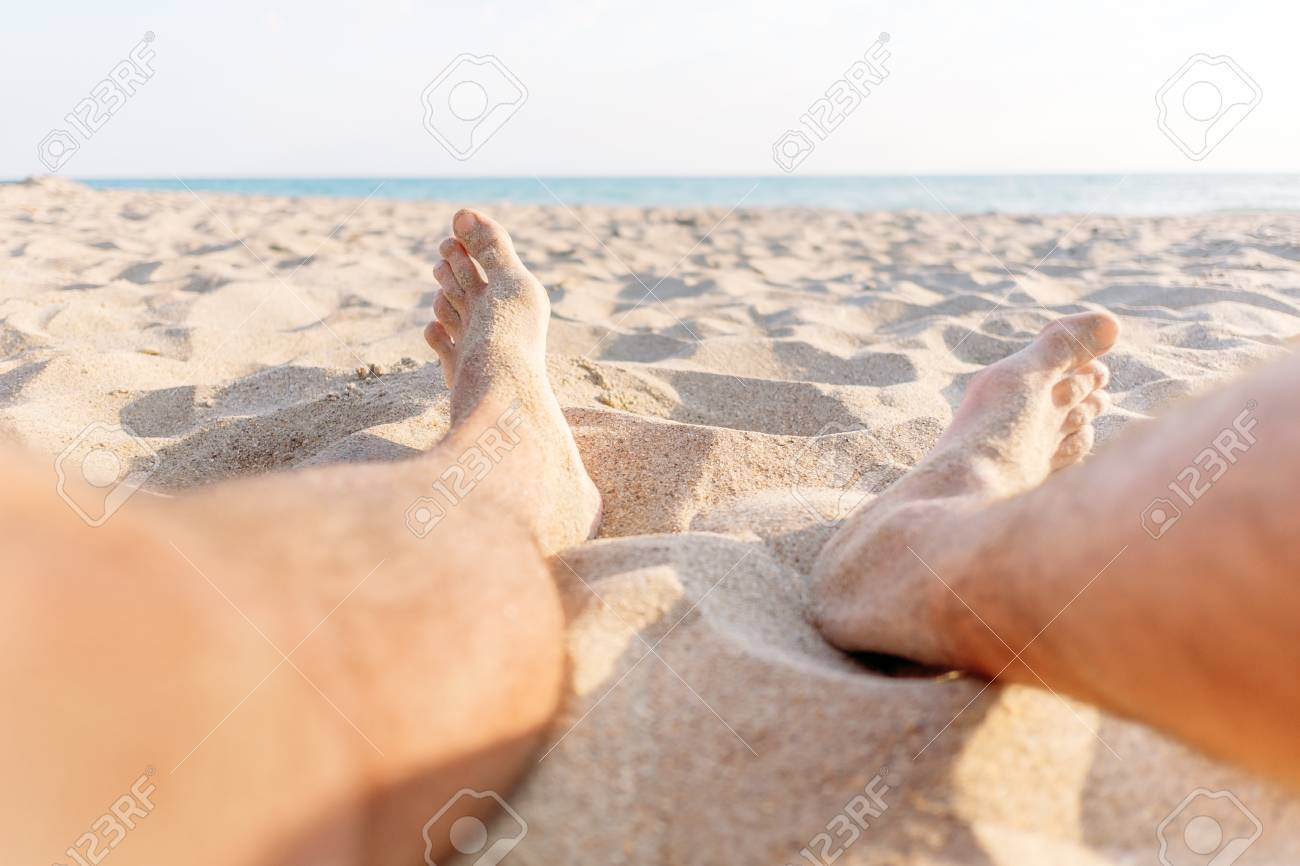 Stock Photo - Young man sitting on sand beach, view of legs, pov image.