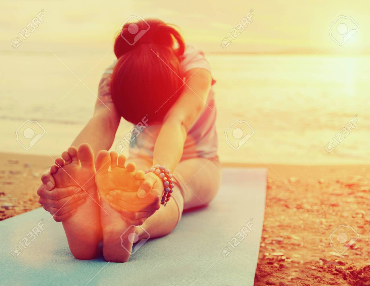 Young woman doing yoga exercise on summer beach at sunset. Image with sunlight effect - 128550411