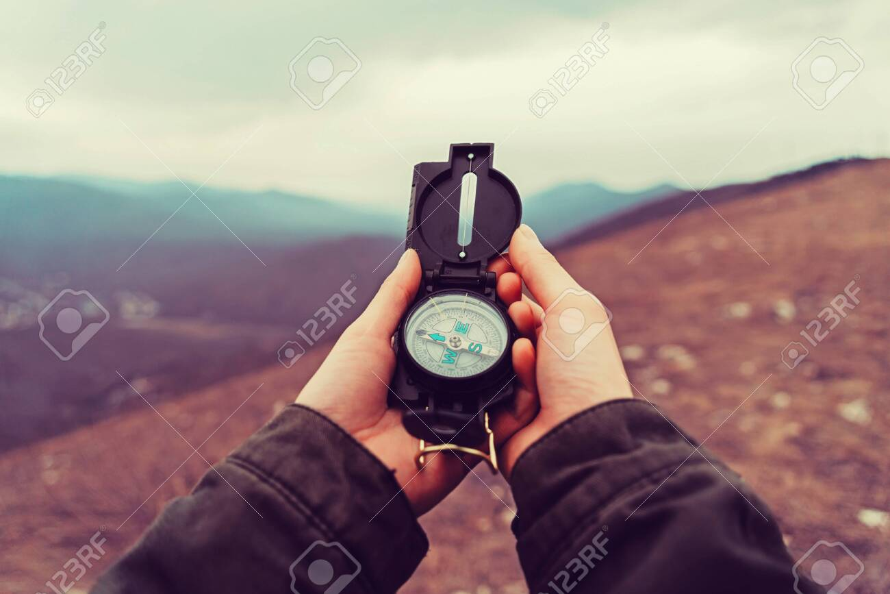 Hiker woman searching direction with a compass in the mountains. Point of view shot - 128515229