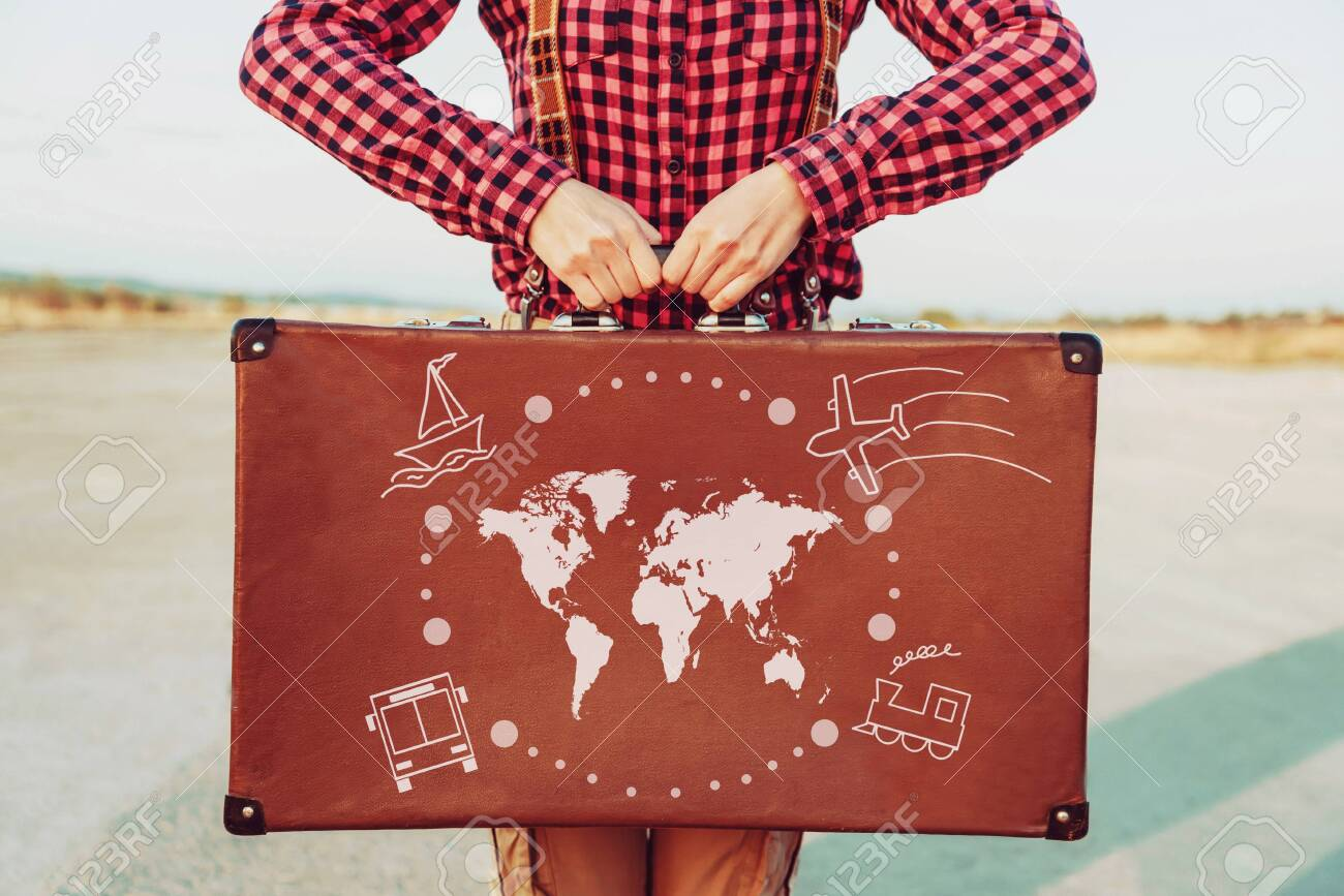 Traveler woman standing with a suitcase. Map of the world and types of transport are painted on suitcase. Concept of travel - 128514119