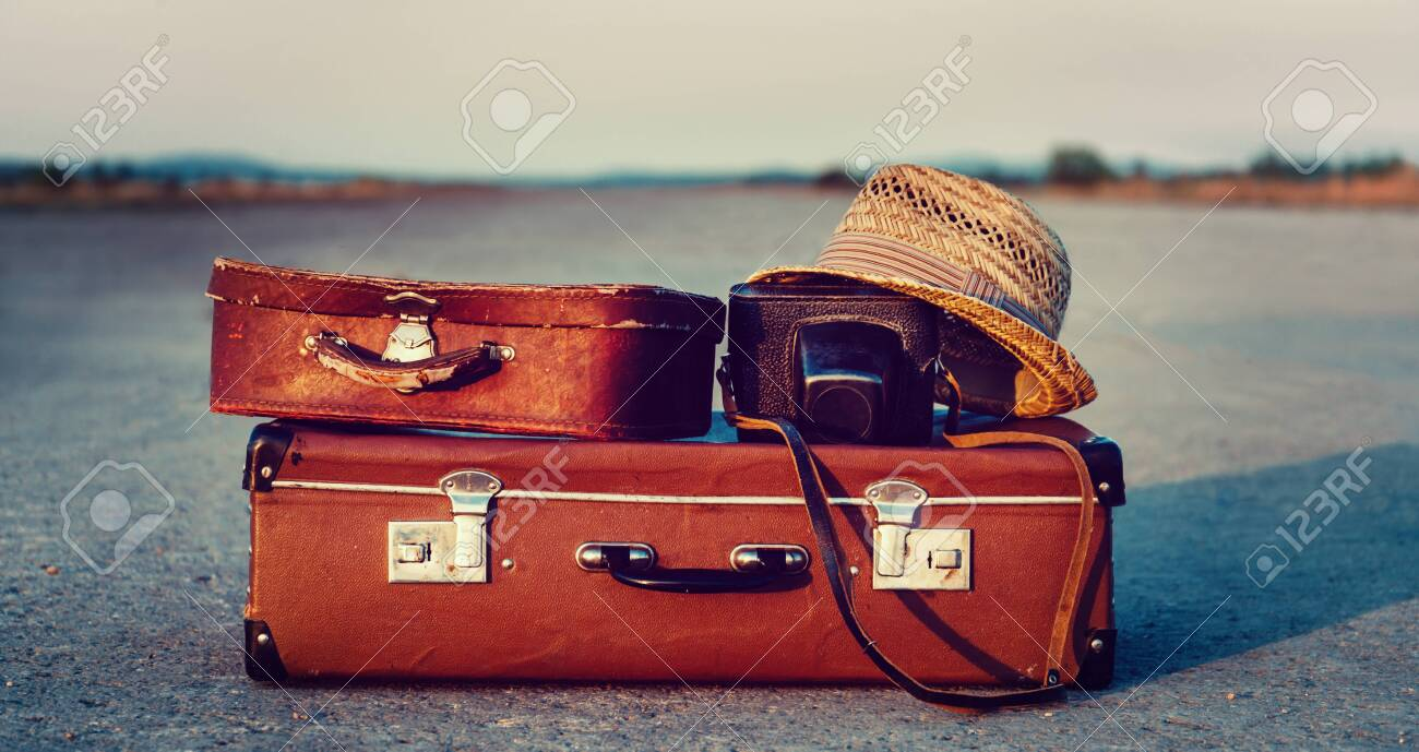 Vintage suitcases, photo camera and hat on road, concept of travel - 128514897