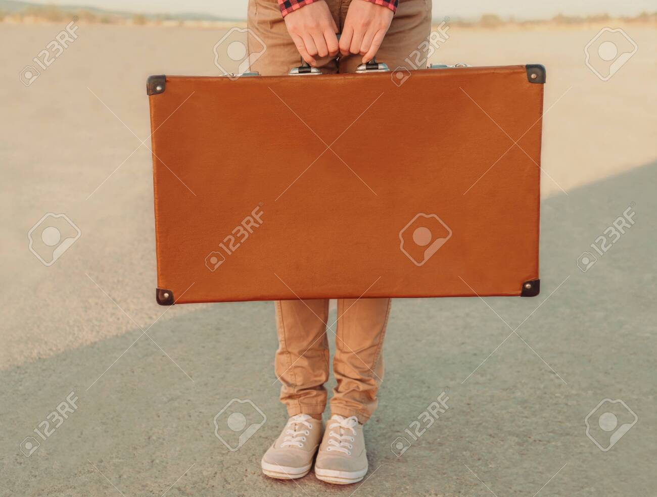 Traveler holding a suitcase, view of hands. Space for text on suitcase - 128517896