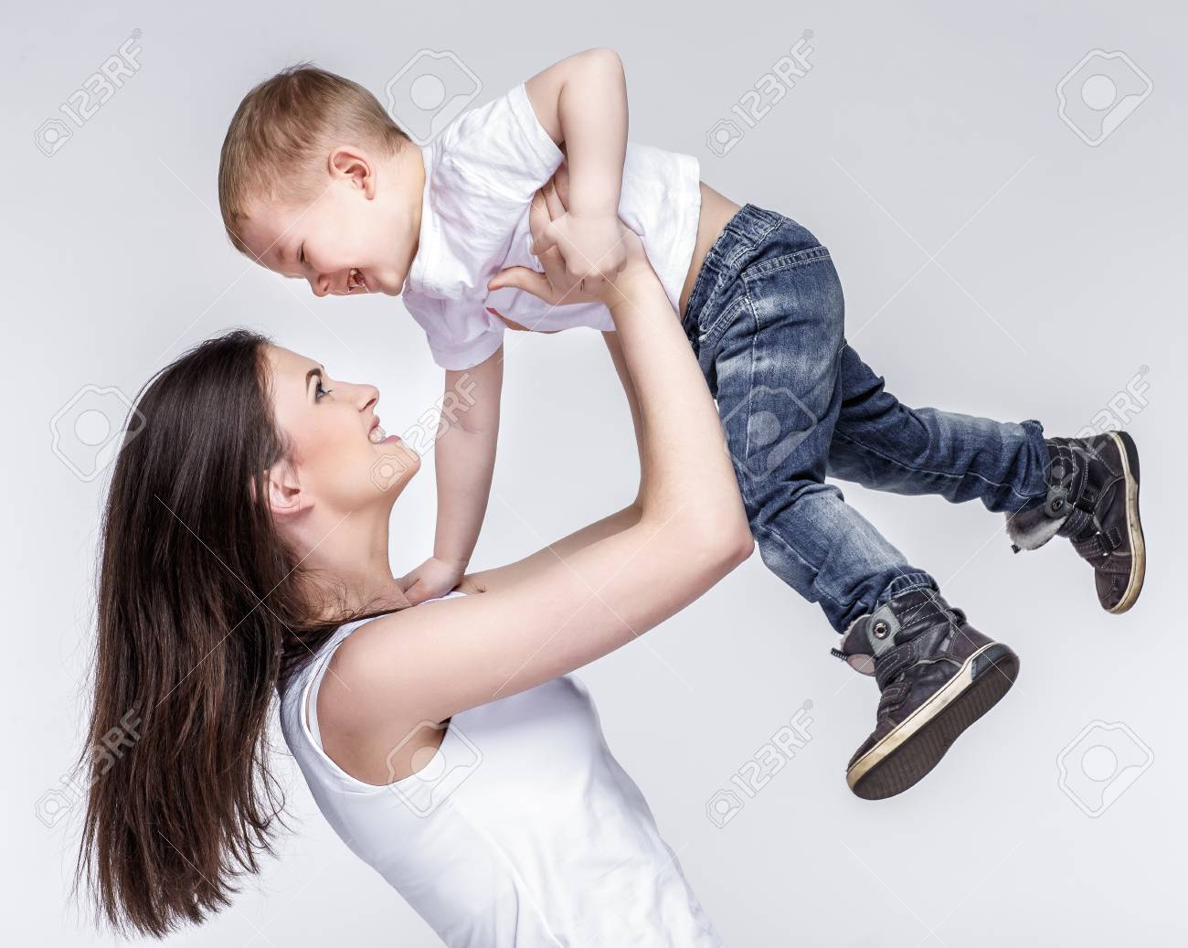 happy young mother with a child on light grey background - 52123572
