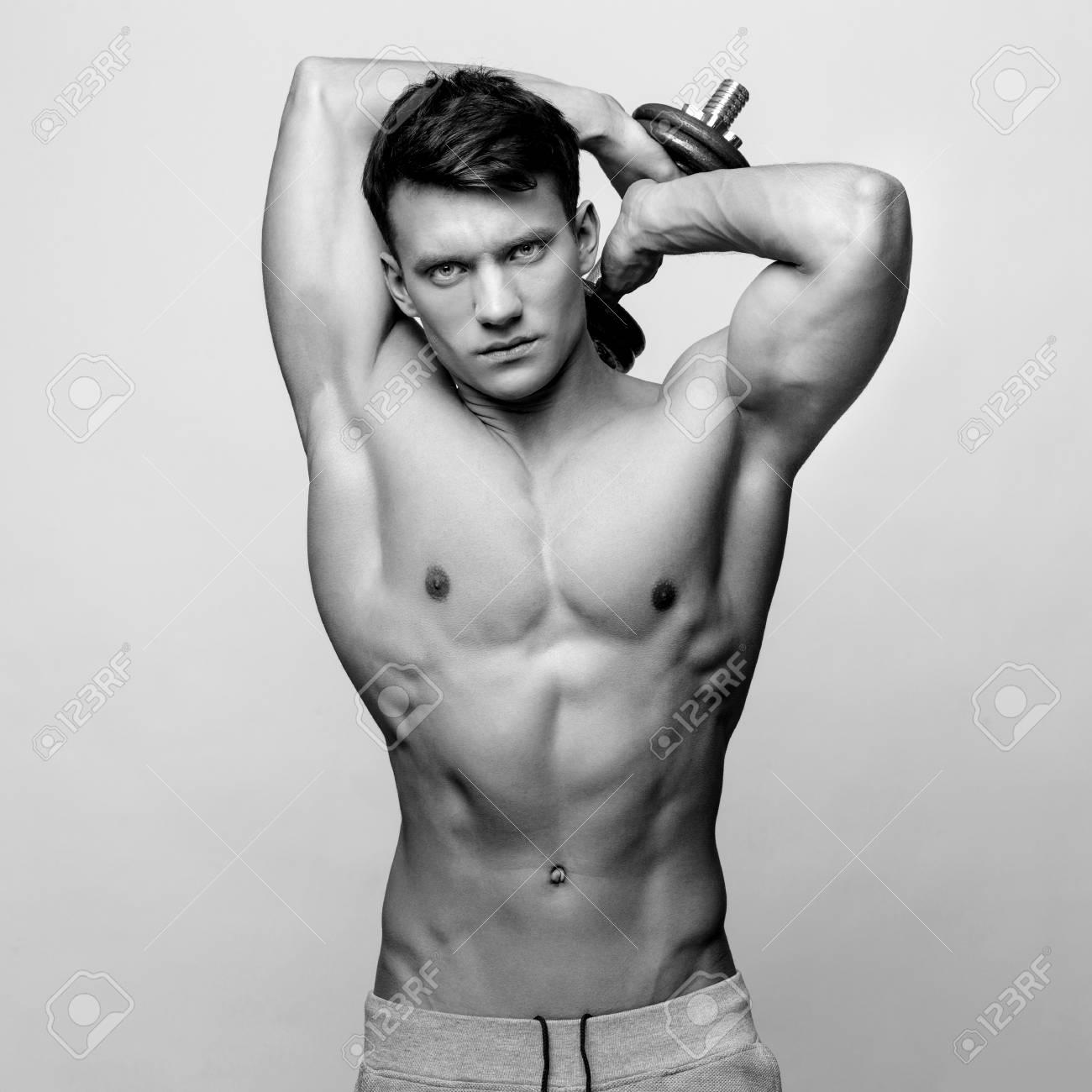 Studio Shot Of Shirtless Bodybuilder Holding Dumbell And Showing