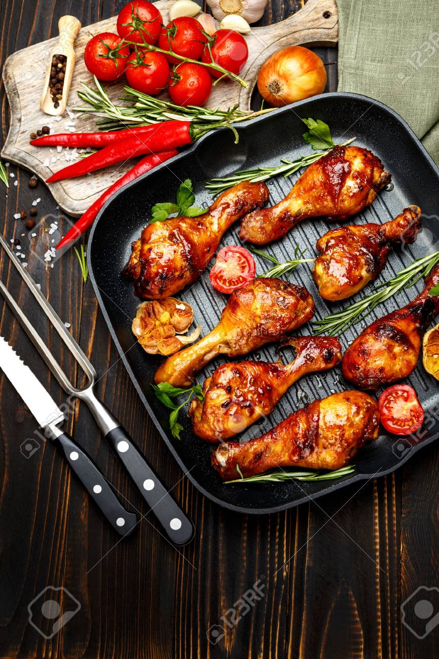 roasted chicken legs with herbs on wooden table - 62136139