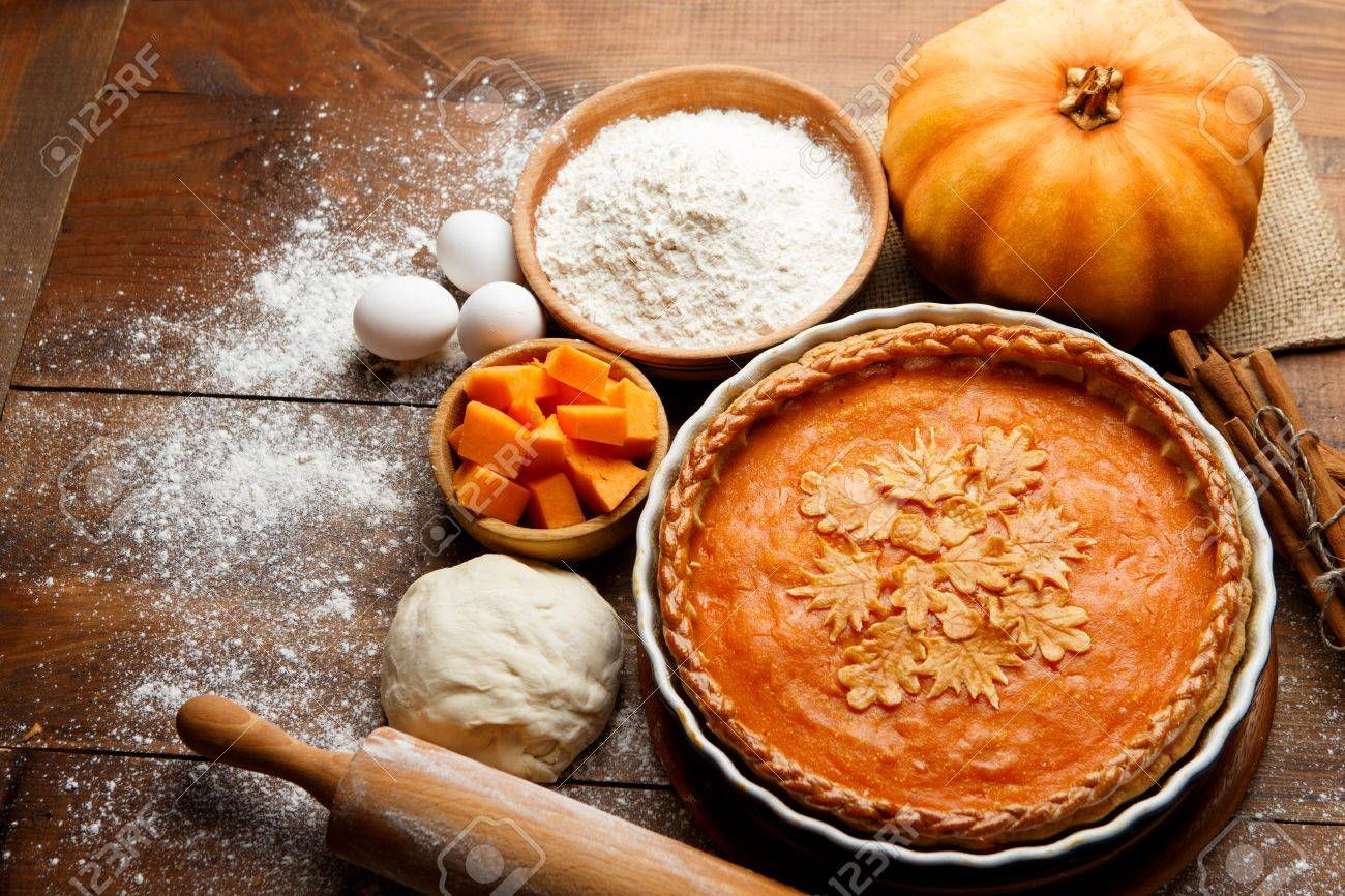 Traditional american fresh round bright orange homemade pumpkin pie in baking dish on wooden table - 65315771