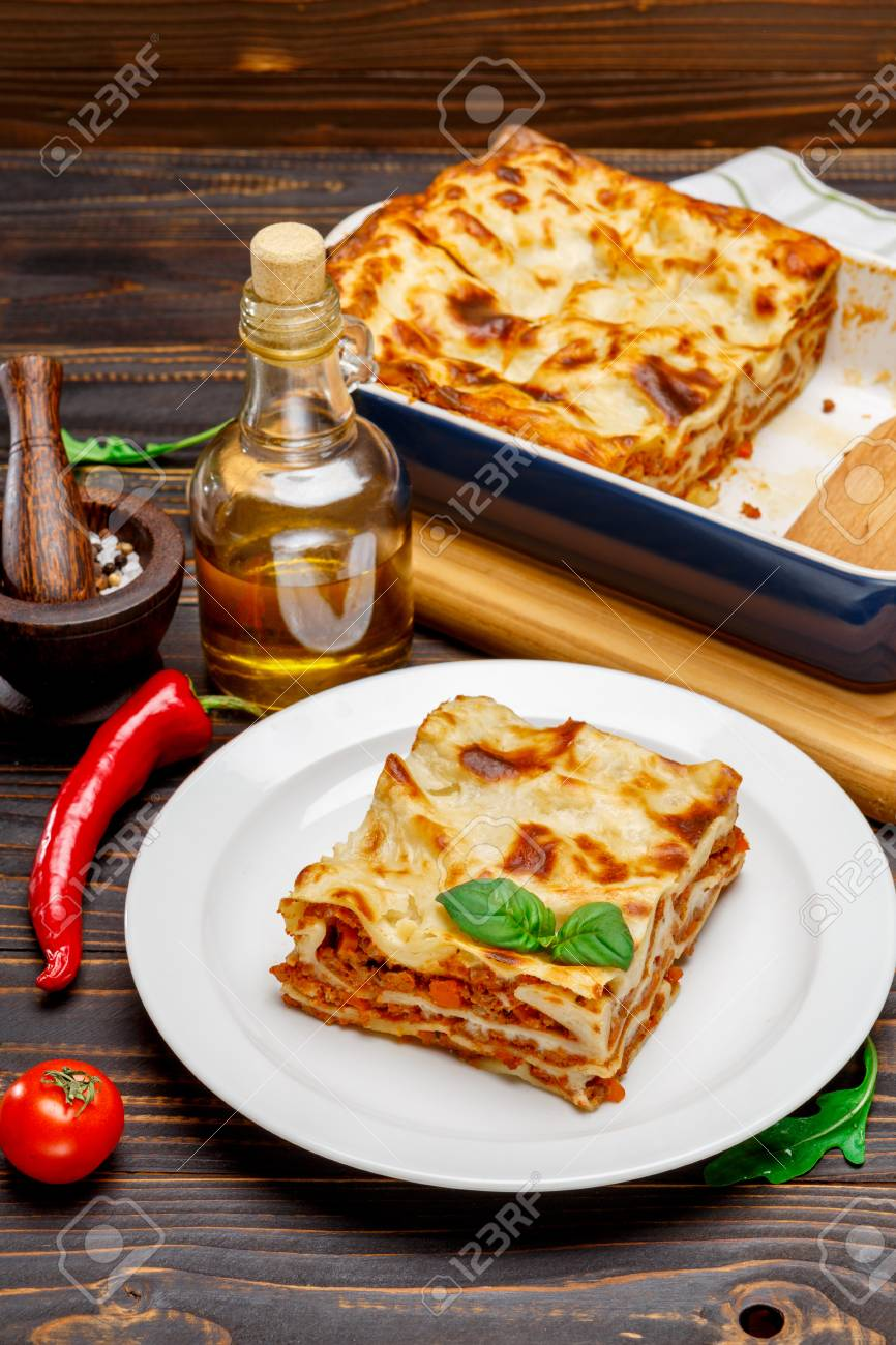 Portion of tasty lasagna on wooden backgound - 78054814