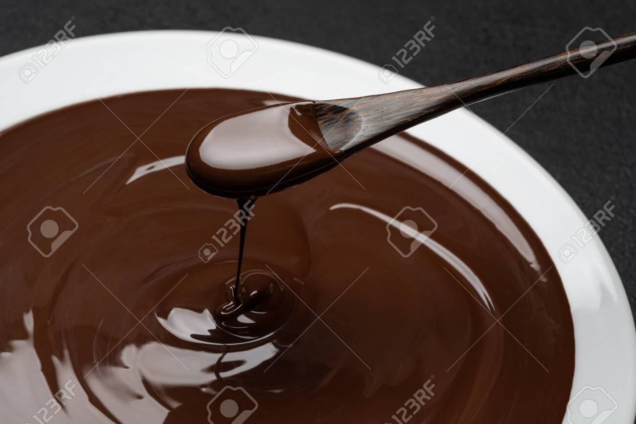 Macro of Melted milk or dark chocolate swirl in plate and spoon on concrete background - 120732543