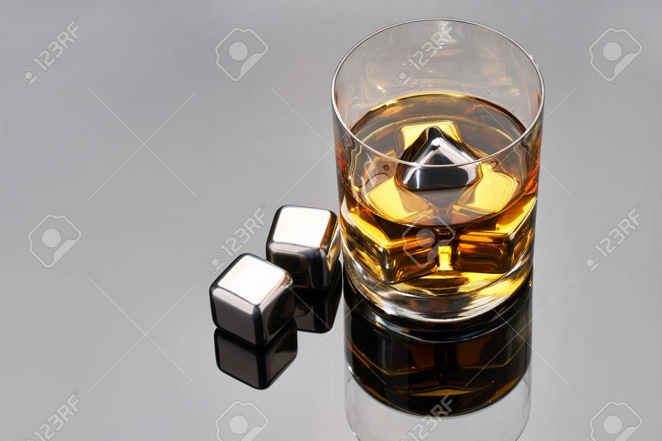 Whiskey with steel cooling cubes on dark glass background - 169835461