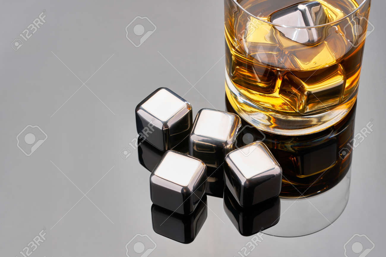 Whiskey with steel cooling cubes on dark glass background - 169835464