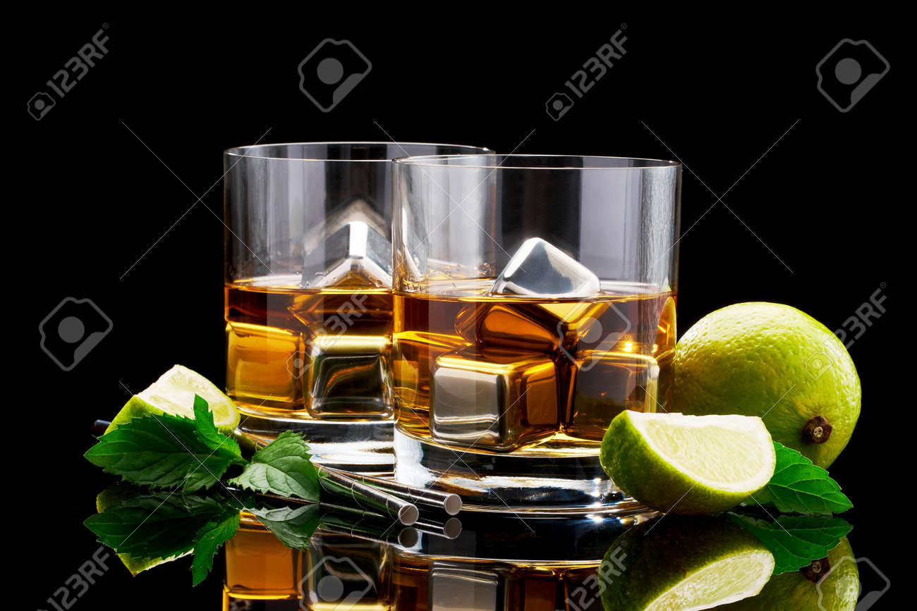 Whiskey with steel cooling cubes on dark glass background - 169835469