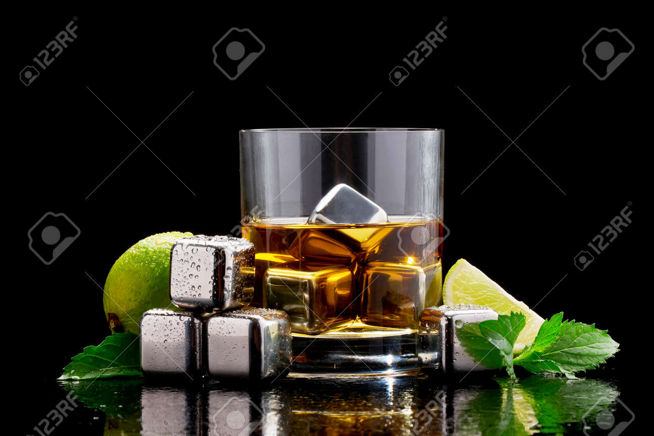 Whiskey with steel cooling cubes on dark glass background - 169835471