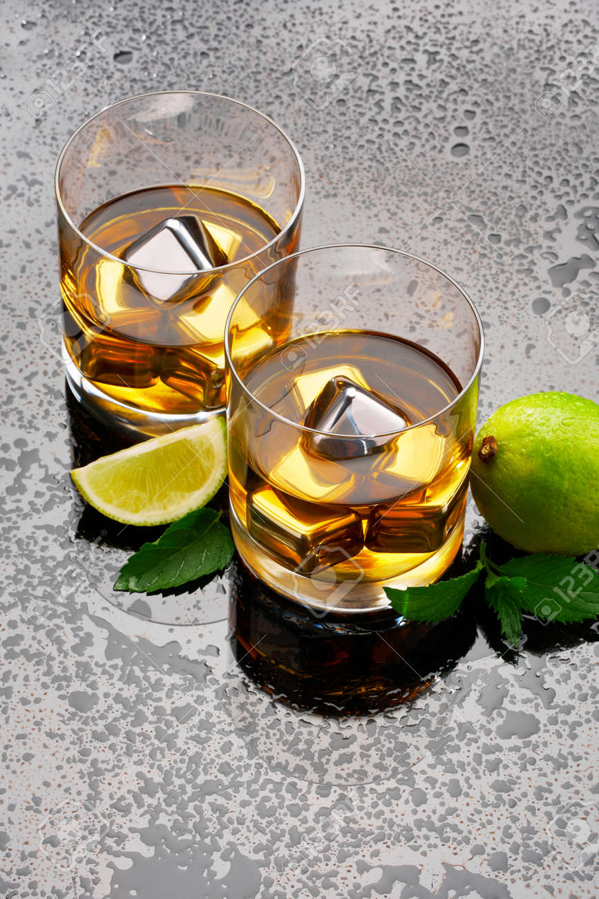 Whiskey with steel cooling cubes on dark glass background - 169835475