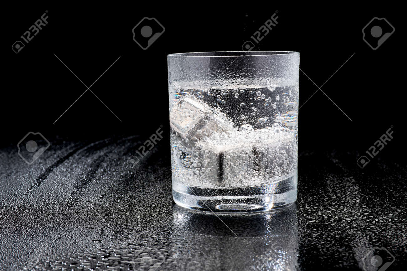 Glass of Soda or Coctail with steel cooling cubes on dark glass background - 169835482