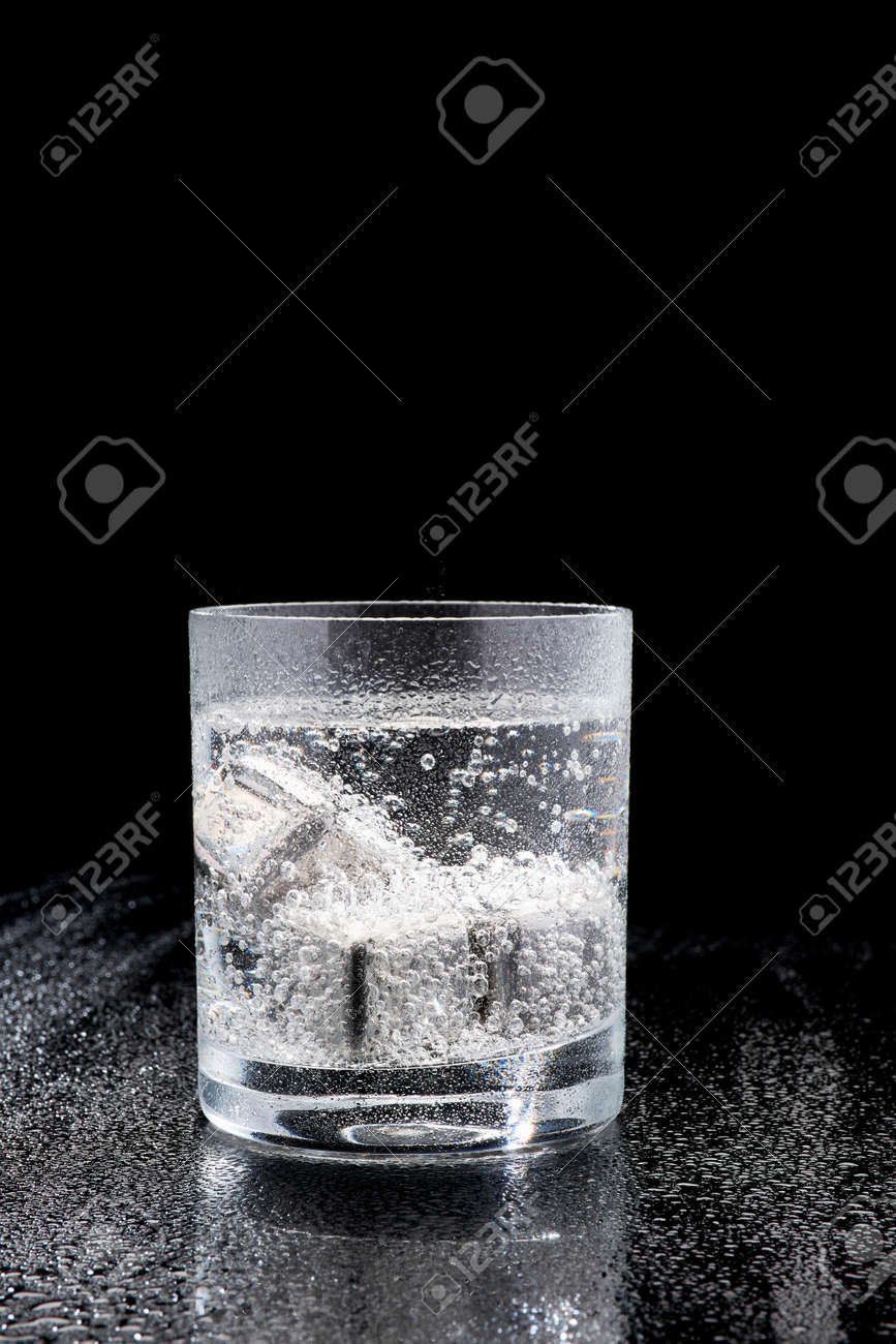 Glass of Soda or Coctail with steel cooling cubes on dark glass background - 169835484